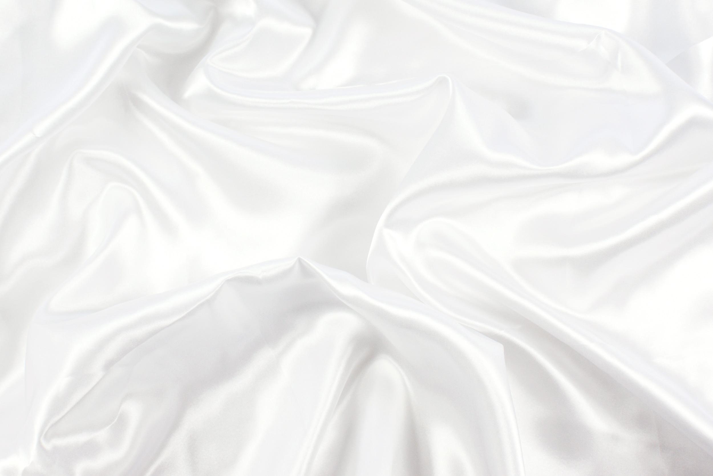 Фото текстура шелк белого цвета на текстильной простыне