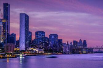 Картинка фон для фотошопа город в рассветные сумерки: горизонт с небоскрёбами, свет огней на синей воде, пурпурное небо с облаками.