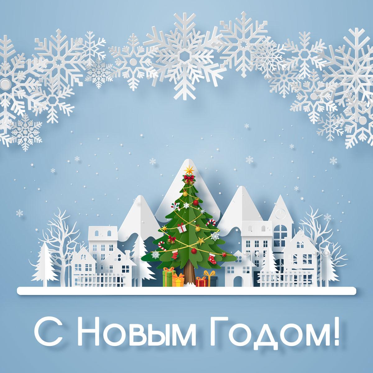 Голубая открытка с зимней ёлкой, снежинками и домами из вырезанной бумаги.