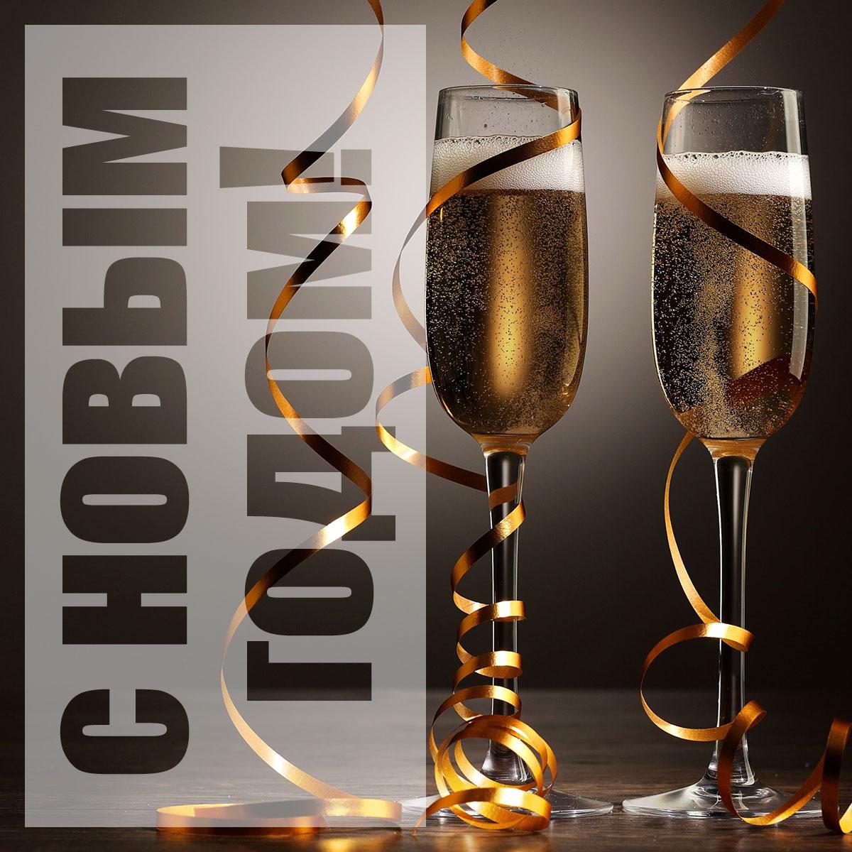 Фотография с надписью под новогодние открытки с двумя бокалами светлого шампанского с золотым серпантином.