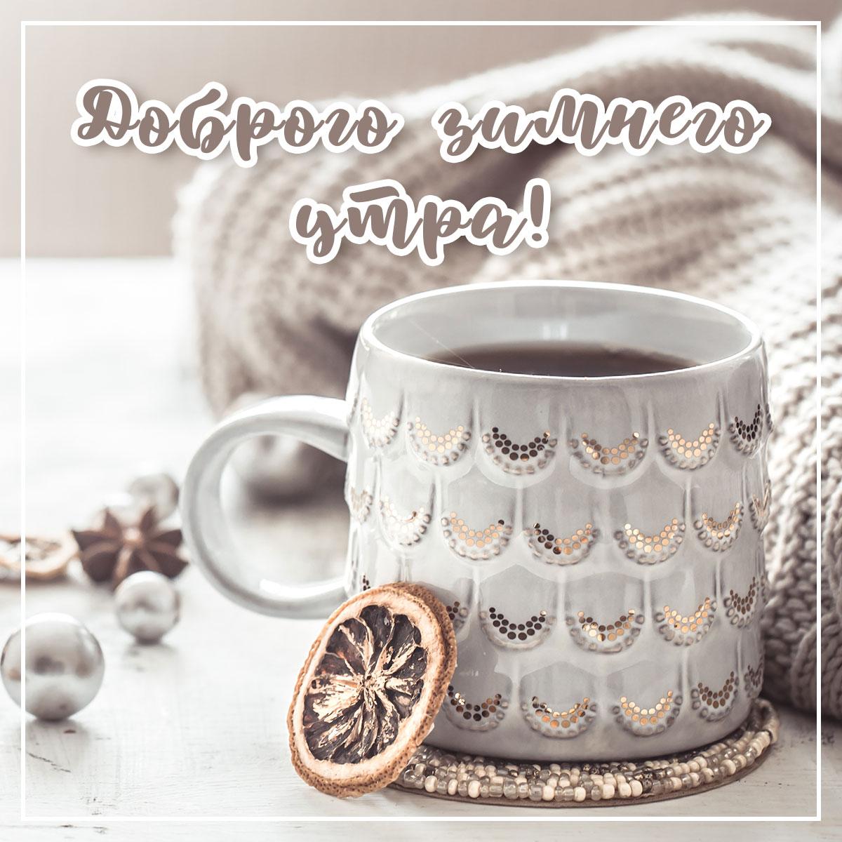 Фотография доброе зимнее утро: натюрморт с надписью, керамической кружкой с чаем, долькой лимона и пледом.