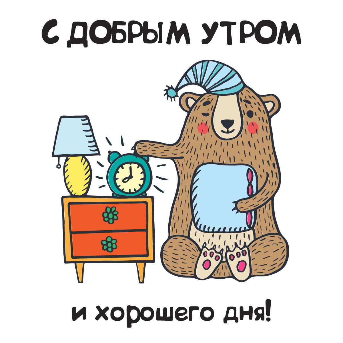 Картинка с надписью доброе утро хорошего дня: мультипликационный медведь в колпаке для сна с подушкой возле тумбочки с лампой и будильником.