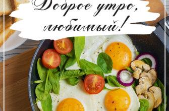Фотография с надписью доброе утро вкусный завтрак из яичницы с помидорами, листьями шпината, грибов и лука в сковороде на деревянной подставке.