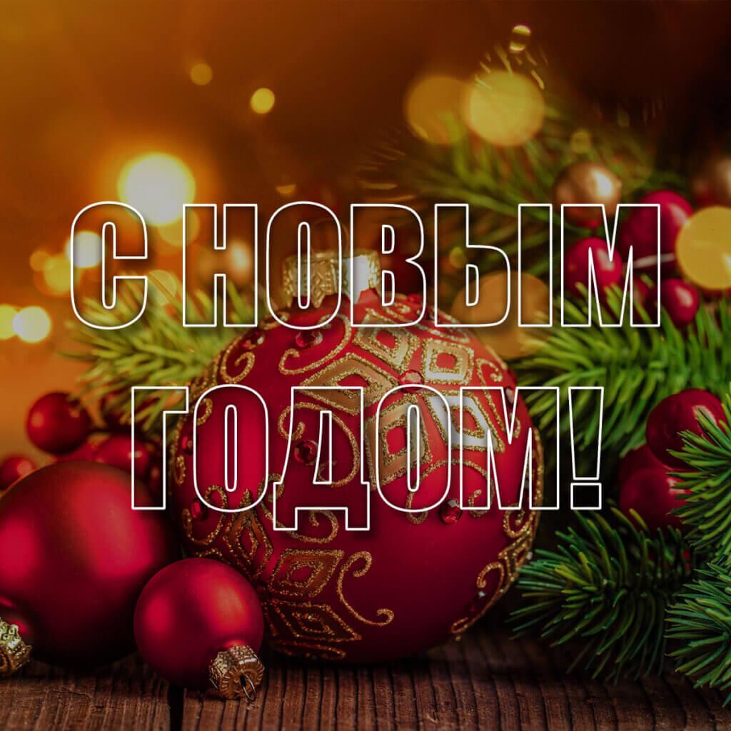 Фотография новогодние ёлочные шары красного цвета с еловыми ветками на янтарном фоне с бликами.
