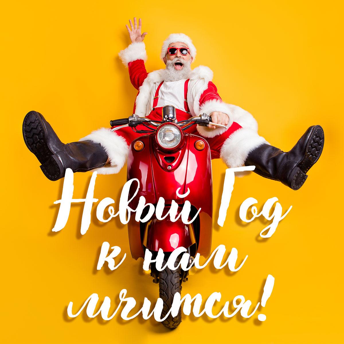 Фотография Санта Клауса в солнечных очках на красном скутере.