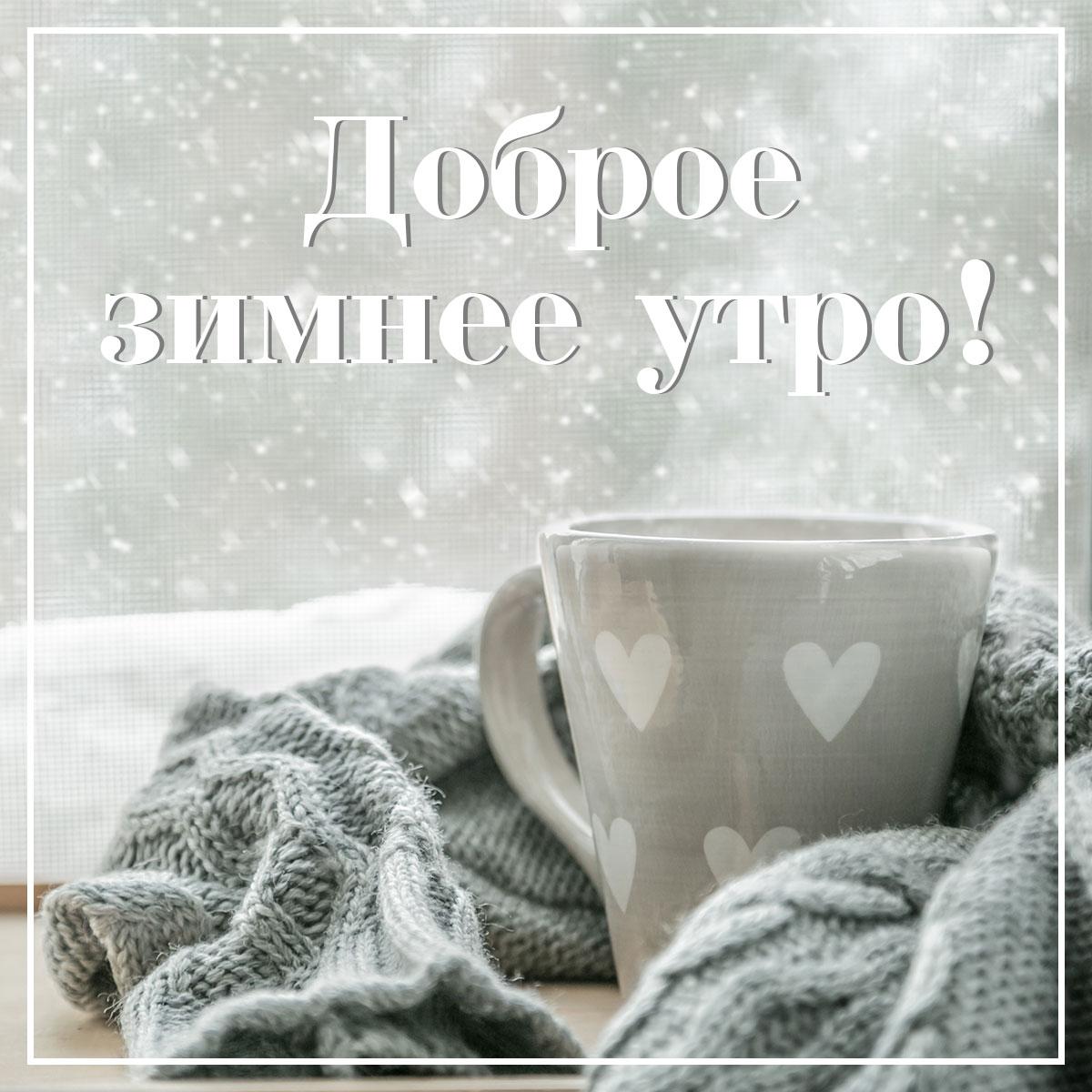 Фото картинка с текстом доброе зимнее утро: серая чайная кружка и вязаный шарф на фоне окна со снегопадом.