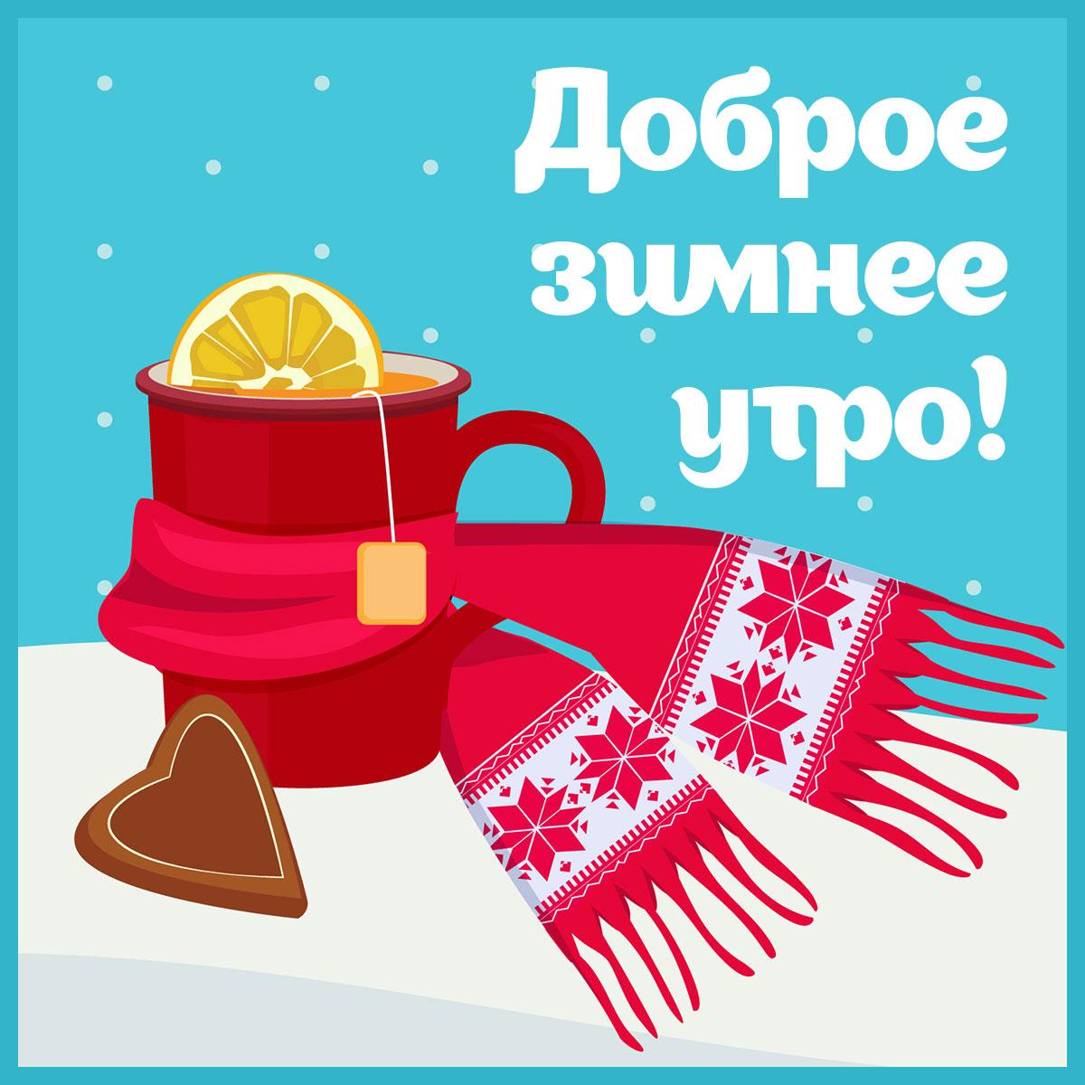 Красная кружка с пакетиком чая и лимоном обернутая шарфом на голубом фоне.