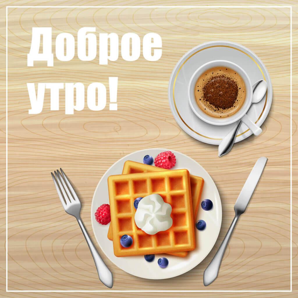 Картинка с текстом доброе утро вкусные бельгийские вафли на тарелке с ножом и вилкой и чашка кофе на блюдечке.