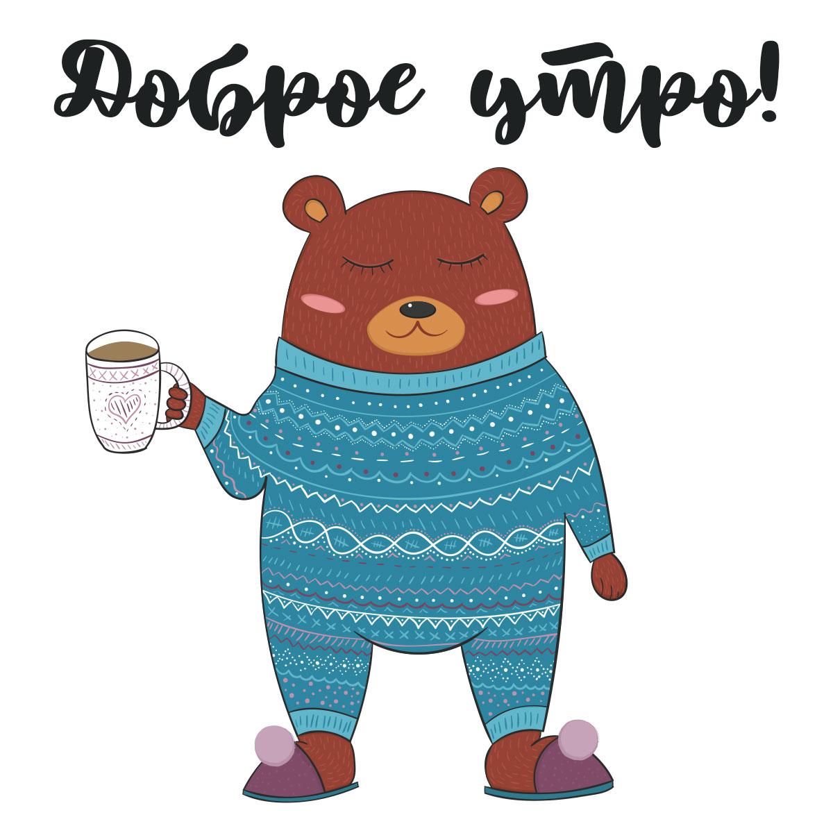 Медведь в сплошной вязаной пижаме с кружкой кофе в лапе.