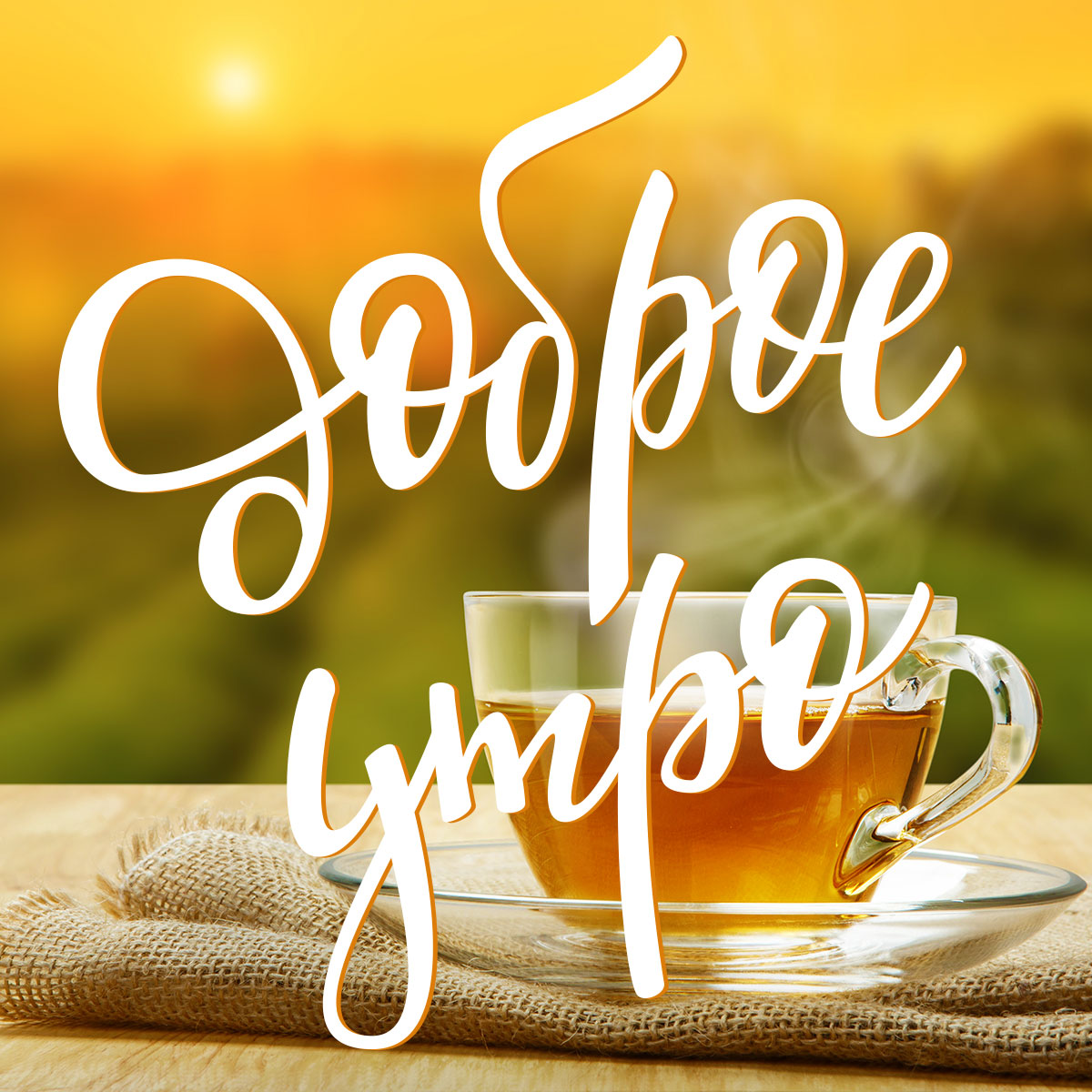 Чай в прозрачной чашке на блюдечке на фоне утреннего пейзажа.