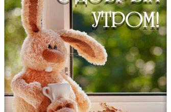 Картинка с надписью с добрым утром: коричневый плюшевый кролик с чайной кружкой и тарелкой с хлебными тостами сидит на подоконнике.
