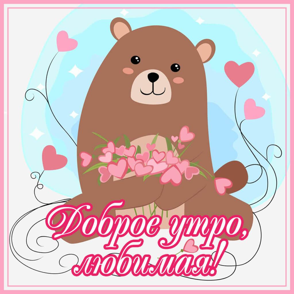 Картинка с надписью доброе утро любимая в прямоугольной розовой рамке с рисунком коричневого медведя с сердечками.
