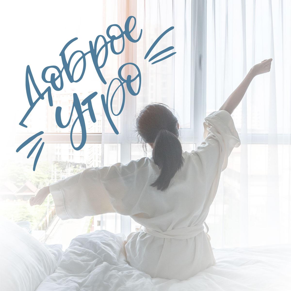 Девушка потягивается сидя на кровати под надписью доброе утро.