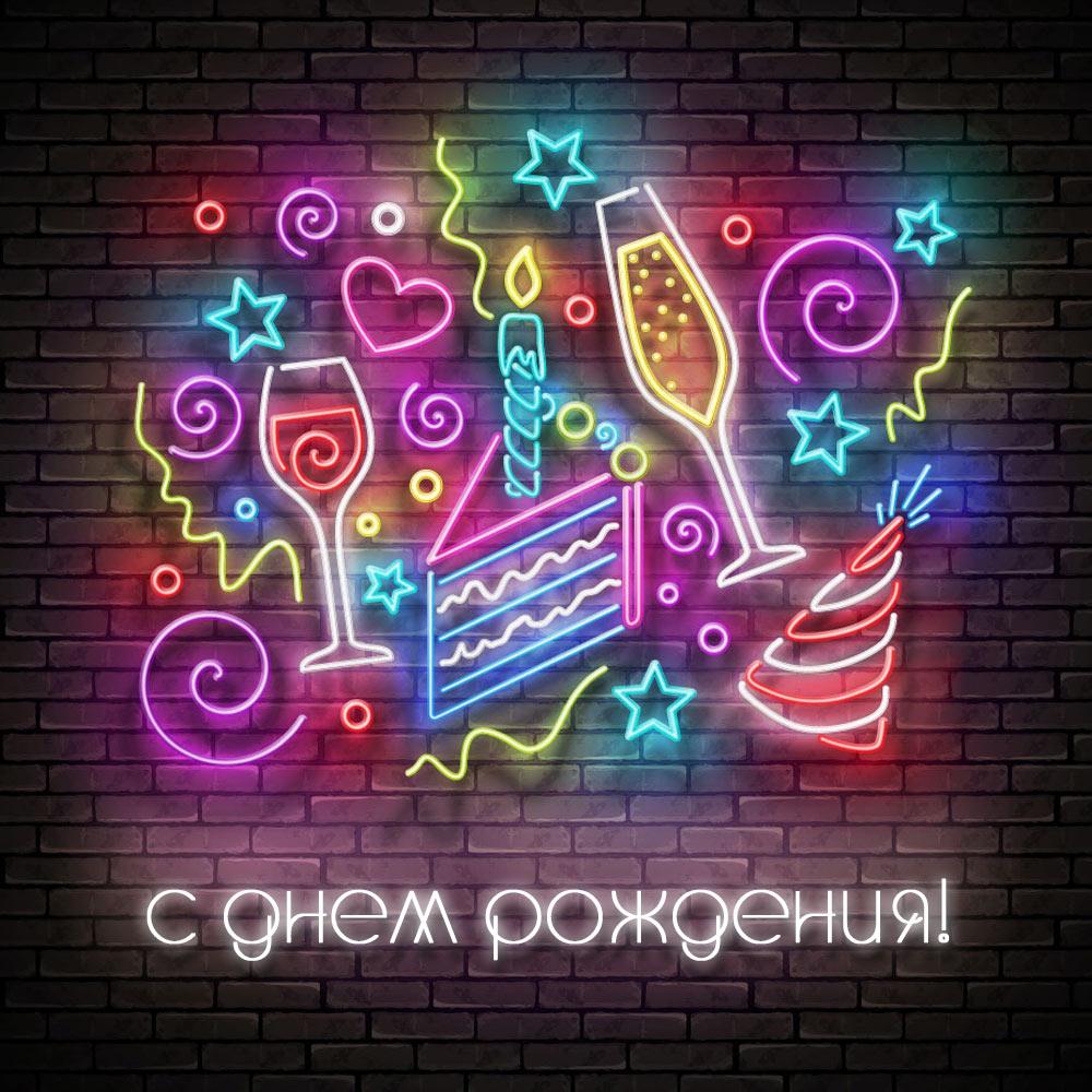 Фраза с днем рождением и неоновые символы на кирпичной стене ночью.