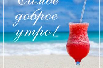 Фото с надписью самое доброе утро с красным коктейлем в бокале на морском пляже.