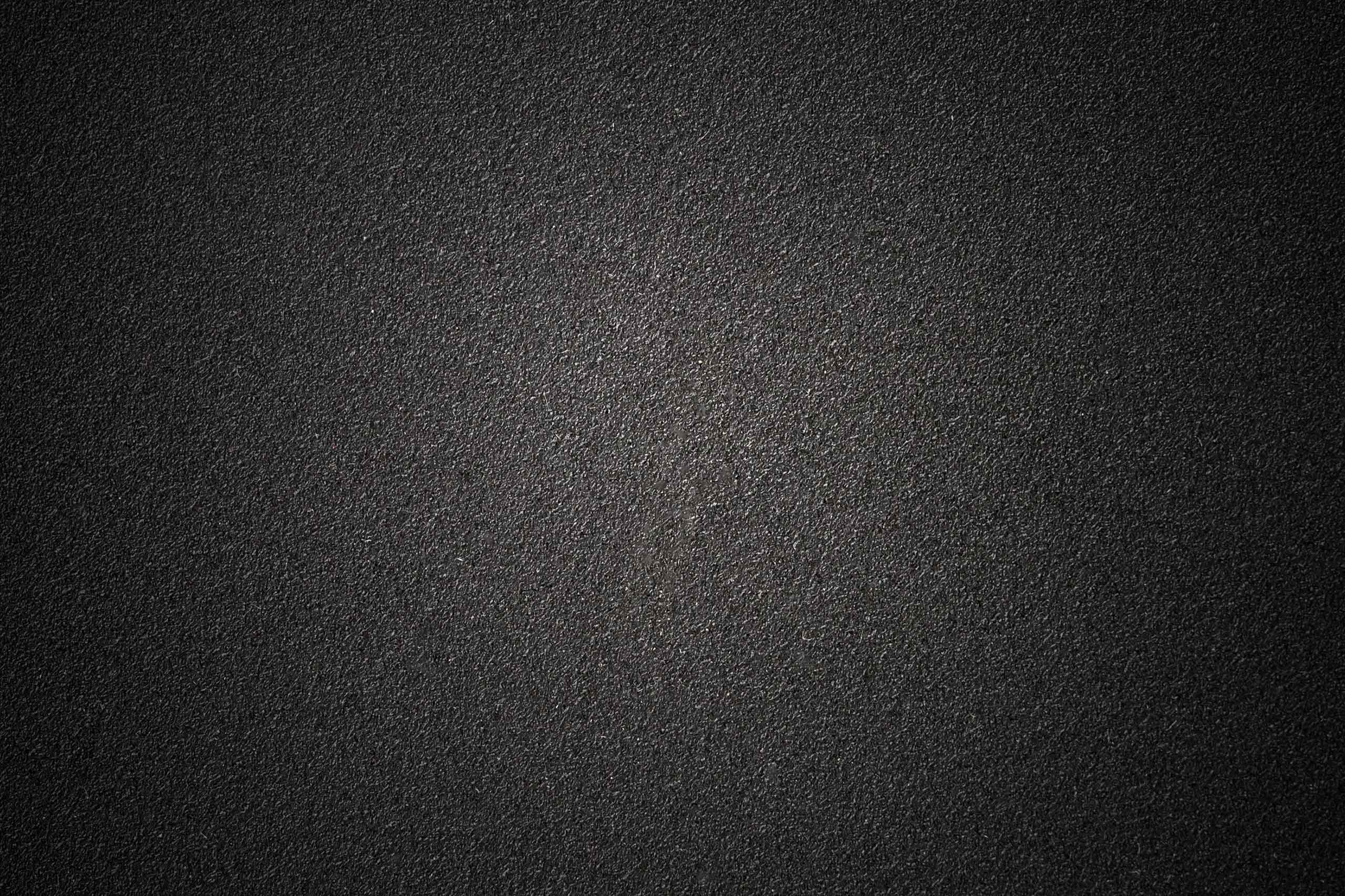 Монохромный темный фон с асфальтовой поверхностью.