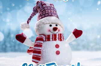 Фотография снеговика в шапке и шарфе на голубом зимнем фоне с надписью весёлых святок!
