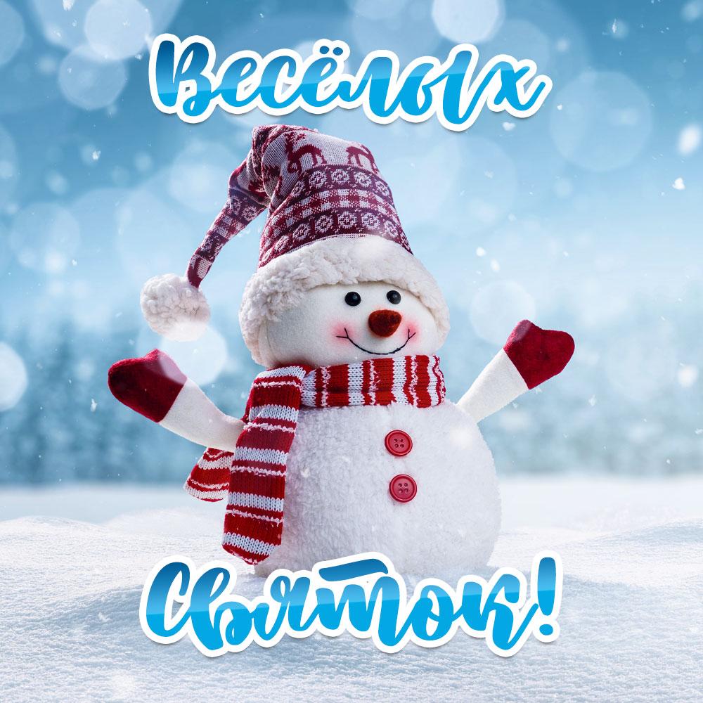 Фото картинка снеговика в шапке и шарфе на голубом зимнем фоне на Святки.